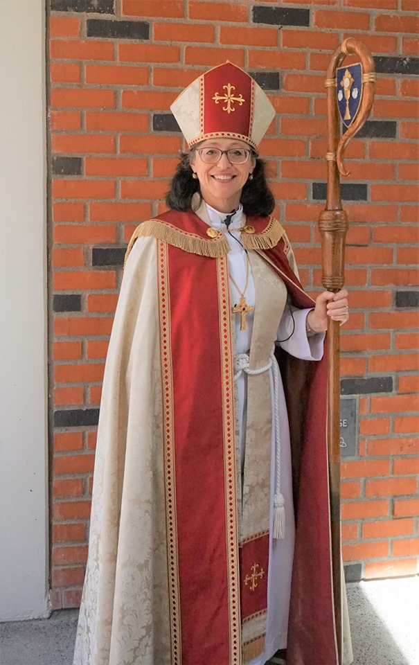 Bishop Megan, wearing a red and cream colored cope and mitre, carrying a wooden crozier.