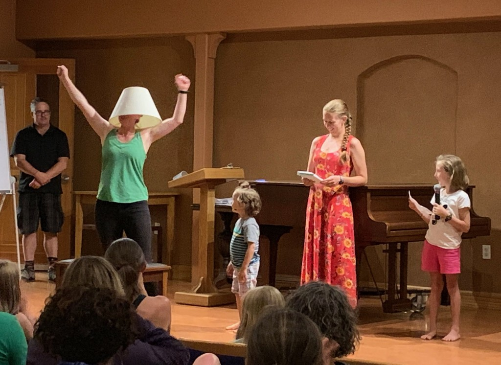 A woman stands on stage with her fists in the air and a lampshade on her head, while two small children and two other adults look on.