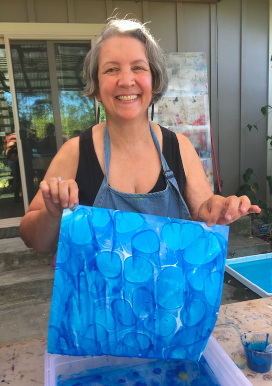 Jocelyn holds a piece of paper marbled with different shades of blue, smiling