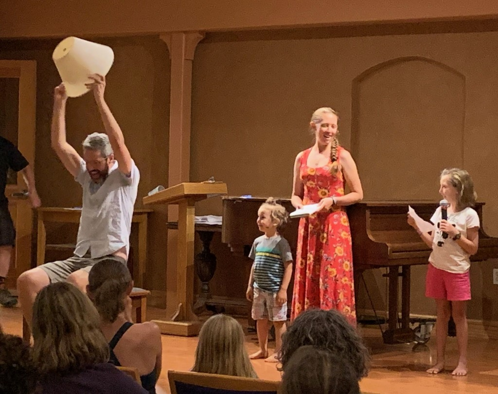 Phil sits on stage holding a lampshade over his head, while two small children and two other adults look on.