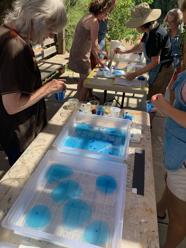 People are gathered around bins of water with blue dye, preparing to marble paper