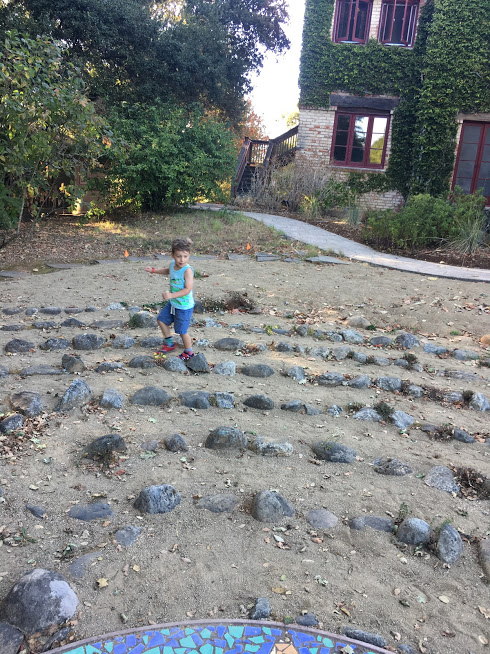 A small child runs through the rocks of the labyrinth