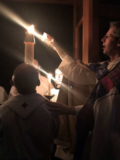 Lighting candles from the paschal candle to process into the church.